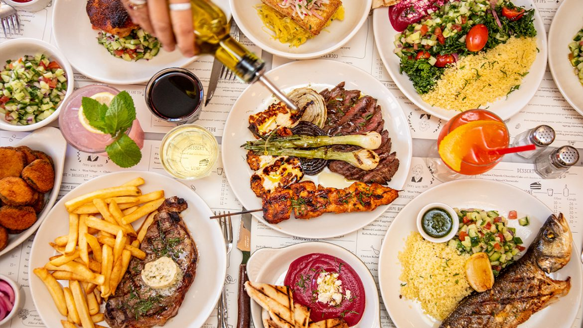 Large table of food and plates with hands grabbing for food, Steak, vegetables