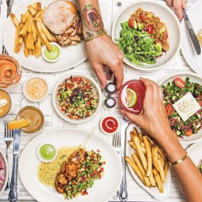 Large table of food and plates with hands grabbing for food