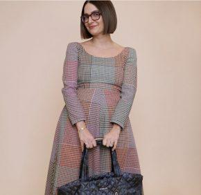Maya posing for a photo with a handbag